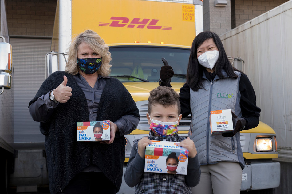 Mayor Dana Ralph of Kent, Washington (left) and Trang Le, a volunteer with both SmartAID and Restart Partners, celebrate the delivery of one million masks for children in Washington State by handing the first box of masks to a local boy. The one million masks are being donated by FLTR, Inc. to child care and youth programs throughout Washington State as part of the Millions of Masks for Children Initiative, a growing nationwide effort to help protect millions of children from COVID-19. FLTR, SmartAID, DHL, SEKO Logistics and other organizations are working together to deliver these masks.